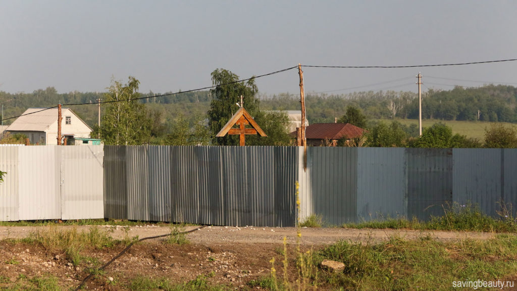 Крест за забором из профлиста в Черниговке Задонского района